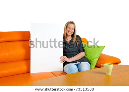 Young attractive smiling woman with blank bill board sitting on sofa