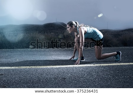 young attractive sport woman posing on start grid style ready for running workout on asphalt road in dramatic harsh light advertising style with lens flare in high performance and energy concept