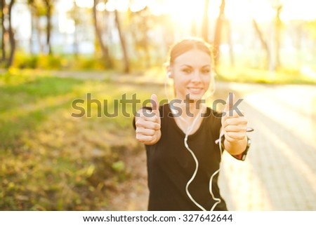 Young attractive sporty female girl with earphones and armband showing thumbs up after successful training on summer evening in park. Sun shining behind model. Copy space. Selective focus on hands