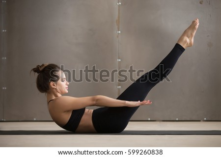 Young attractive sporty woman practicing yoga or fitness, doing boat exercise, working out, wearing black sportswear, cool urban style, full length, grey studio background, side view  #599260838