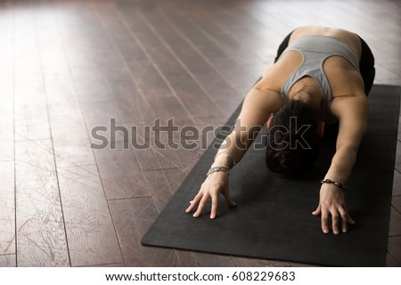 Young attractive sporty woman practicing yoga, sitting in Child exercise, Balasana pose, working out, wearing sportswear, studio background, wooden floor, copy space, view from above