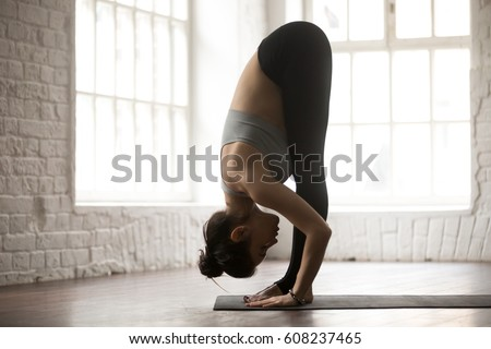 Young attractive sporty woman practicing yoga, standing forward bend exercise, head to knees, uttanasana pose, working out, wearing sportswear, white loft studio background, full length, side view