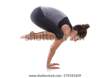 Young attractive sporty woman practicing yoga, standing in Bakasana exercise, Crane pose, working out, wearing sportswear, grey tank top, black pants, full length, isolated, white studio background