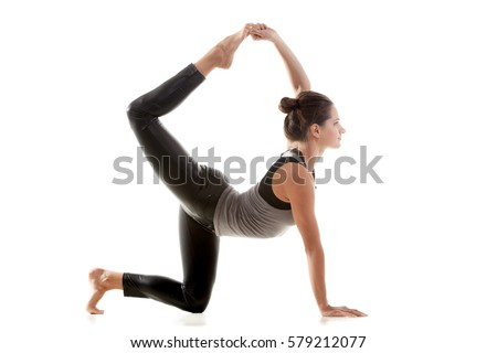 Young attractive sporty woman practicing yoga, standing in Bird dog pose, tiger exercise, working out, wearing sportswear, grey tank top, black pants, full length, isolated on white studio background