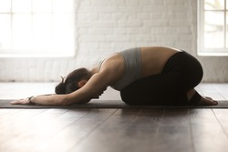 Young attractive sporty yogi woman practicing yoga concept, sitting in Child exercise, Balasana pose, working out, wearing black sportswear, full length, white loft studio background, side view