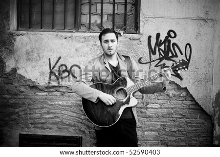 Young attractive street artist playing guitar.
