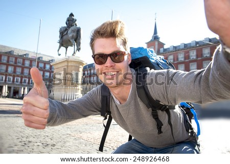 young attractive student backpacker tourist taking selfie photo with mobile phone outdoors enjoying holidays travel destination in tourism and exploring concept