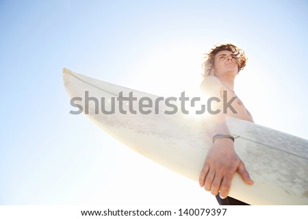 Young attractive surfer sports man wearing a neoprene rubber diving suit and looking at the horizon while carrying his surfing board during a sunny day against the intense blue sky.