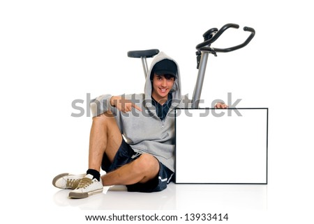 Young attractive teenager in front of fitness bike, with advertising board. Studio shot, white background. - stock photo