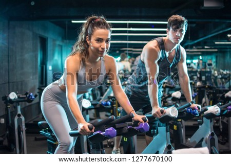 Young attractive woman and handsome man  doing cardio workout cycling bikes in the gym