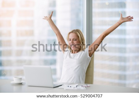 Young attractive woman at a modern office desk, with laptop, stretching her arms with extreme joy special prize winner, office holiday party, found a job, got a date invitation, end of the working day