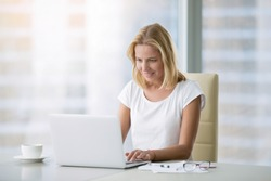 Young attractive woman at a modern office desk, working with laptop, free online classes for interest, stay-at-home mom starting an online business, internet marketing, remote job, lady- blogger