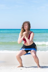 Young attractive woman at beach working out with elastics resistance band doing squats exercise by ocean or sea in Santa Rosa, Florida