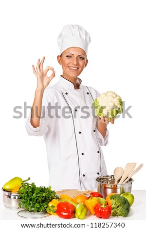 Young attractive woman chef showing OK gesture. Variety of fresh vegetables on table. Studio shot, white background