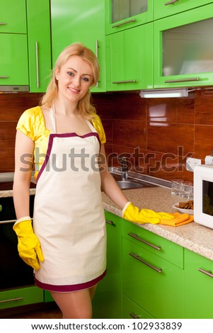 young attractive woman clean the kitchen ( green color )