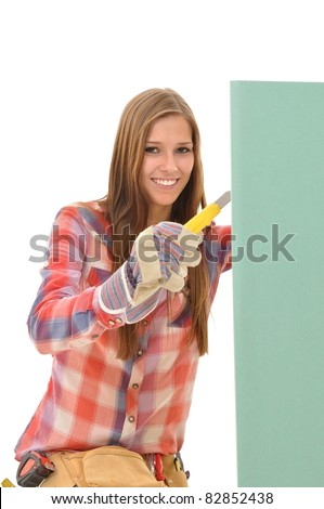 Young attractive woman cutting a green gypsum board
