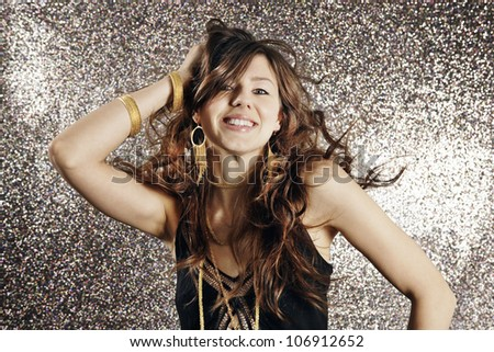 Young attractive woman dancing against a silver glitter background in a night club.
