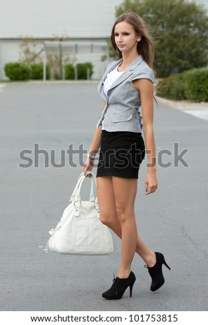 Young attractive woman, dressed in black and white, walking holding bag.