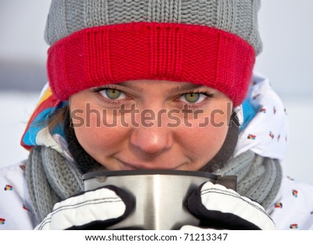 Young attractive woman drink hot tea from a mug in the winter.