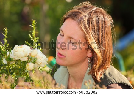 Young attractive woman enjoys the flavor of a rose