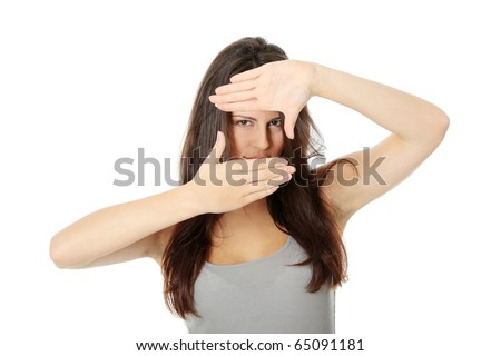 Young attractive woman framing her face with hands, over white