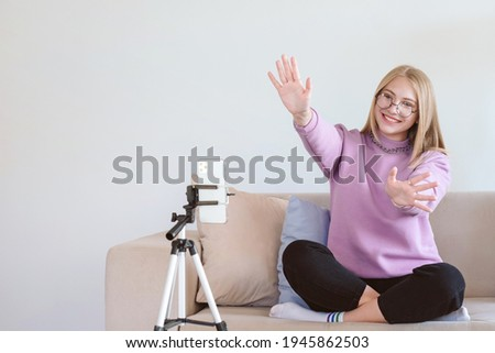 Young attractive woman greeting followers. Blogger or vlogger recording video on mobile phone at home and making content for internet. Human on white background with text place. Foto stock ©