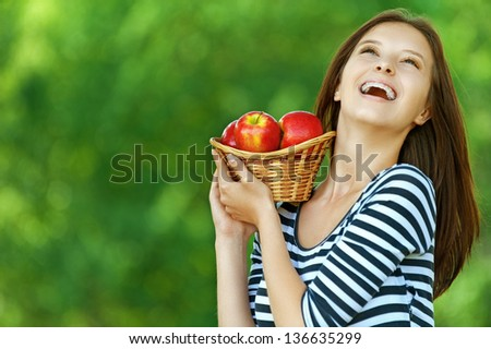 Young attractive woman holding basket with apples, against green of summer park.