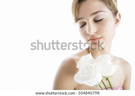 Young attractive woman holding three white roses next to her lips, smiling on a white background.