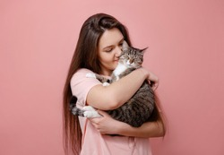 young attractive woman hugging cat in hands, pink background, girl kissing cat