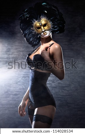 Young attractive woman in mask over dark background #114028534