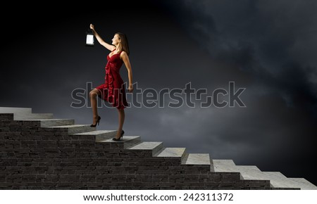 Young attractive woman in red dress with lantern walking in darkness #242311372