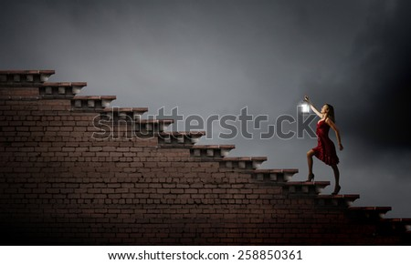 Young attractive woman in red dress with lantern walking in darkness #258850361