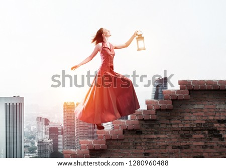 Stock Photo Young attractive woman in red dress with lantern walking up staircase. Mixed media