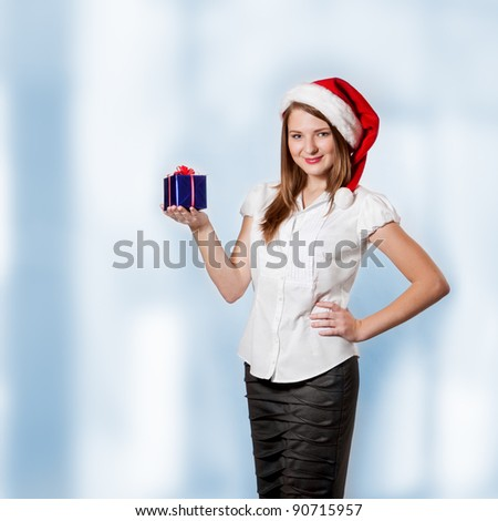Young attractive woman in Santa Claus hat holds christmas gift