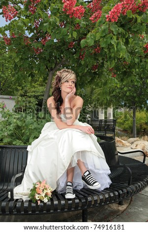 young attractive woman in sitting under colorful tree in a wedding dress
