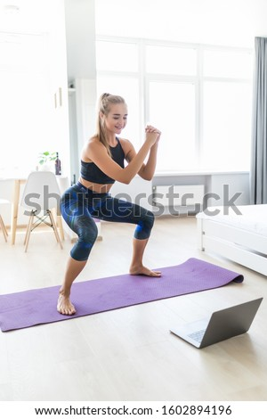 Young attractive woman in sportswear making deep sumo squats in living room while watching fitness online video on laptop. Lady doing exercises for maintaining optimum weight and good physical shape