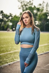 Young attractive woman in stylish sport clothing at football field. Sporty model girl outside.