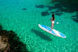 Young attractive woman in the sea on the Stand Up Paddle Board. SUP. Healthy lifestyle.