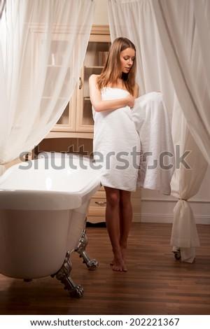 Young attractive woman in towel posing in bathroom interior