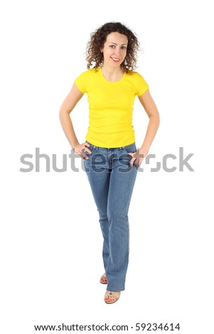 young attractive woman in yellow shirt and jeans standing, hands on hips isolated on white