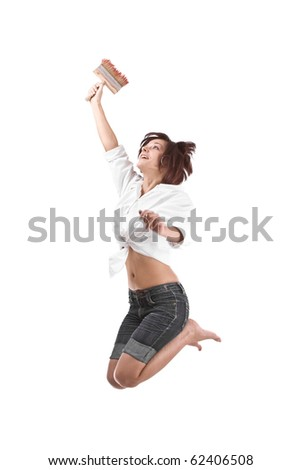 Young attractive woman jumping and holding a paintbrush ready for paint