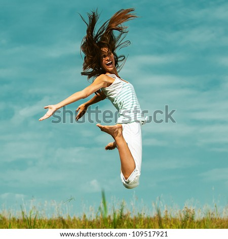 Young attractive woman jumping in sky, against green of summer park.
