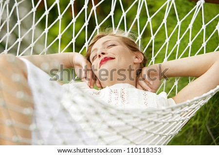 Young attractive woman laying and relaxing on a white hammock in a garden.