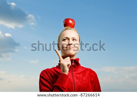 Young attractive woman outdoor holding red apple on her head and thinking about something with a blue sky on a background