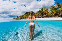 Young attractive woman posing in transparent blue ocean. Swimming in blue water at Mauritius
