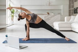Young attractive woman practicing yoga and stretching body at home using laptop for online class or virtual tutorials. Girl standing in Utthita parsvakonasana exercise, doing Side Angle pose. Wellness