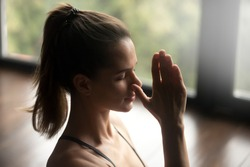 Young attractive woman practicing yoga, doing Alternate Nostril Breathing exercise, nadi shodhana pranayama pose, working out, indoor close up, yoga studio, side view. Mindful healthy life concept