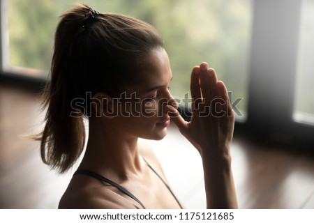 Young attractive woman practicing yoga, doing Alternate Nostril Breathing exercise, nadi shodhana pranayama pose, working out, indoor close up, yoga studio, side view. Mindful healthy life concept #1175121685