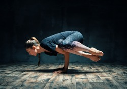 Young attractive woman practicing yoga doing side crane pose in dark room. Parsva Bakasana exercise. balance and recreation concept