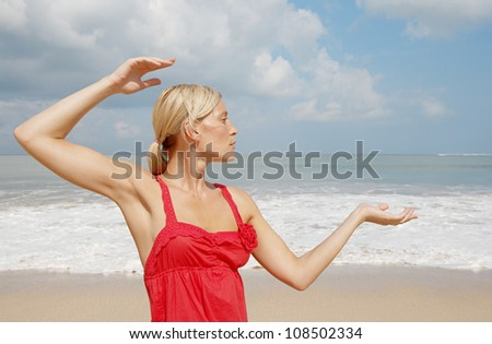 Young attractive woman practicing yoga on a beach. - stock photo